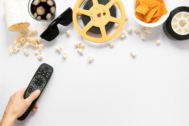 Elementos de filme sobre fundo branco e pessoa segurando um controle remoto da tv