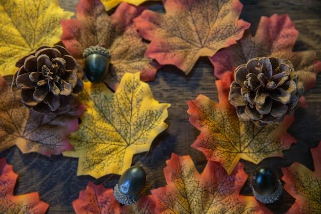 Elementos de outono como folhas, bolotas e pinha na madeira