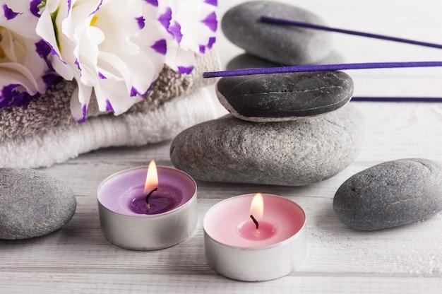 Elementos de spa com toalhas, velas acesas e palitos de aroma roxo