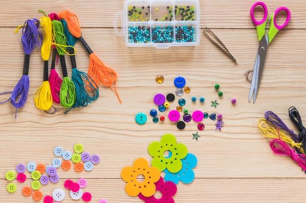 Elementos decorativos coloridos com tesoura na mesa de madeira