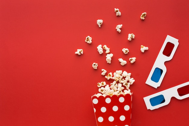 Elementos do cinema vista superior sobre fundo vermelho, com espaço de cópia