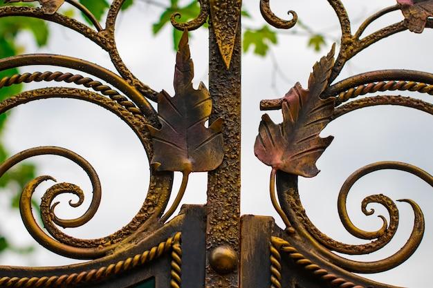 Elementos ornamentados de ferro forjado na decoração do portão de metal.