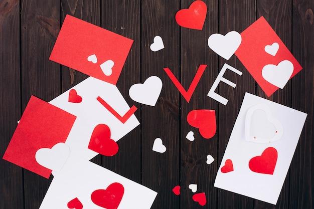 Elementos para o cartão do dia dos namorados encontram-se na mesa de madeira