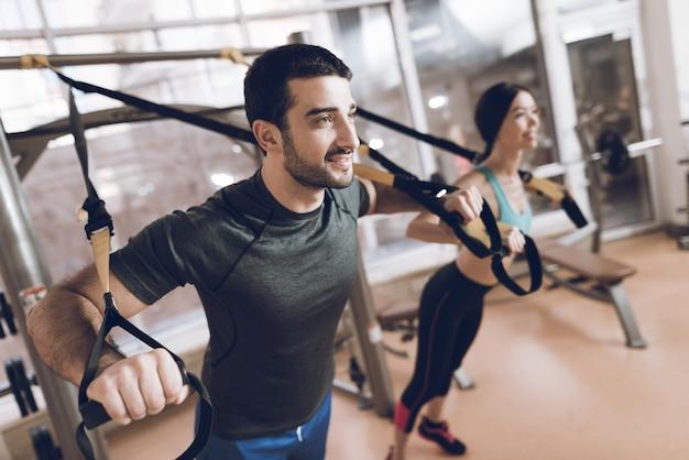 Eles estão no ginásio e se concentram nos exercícios.