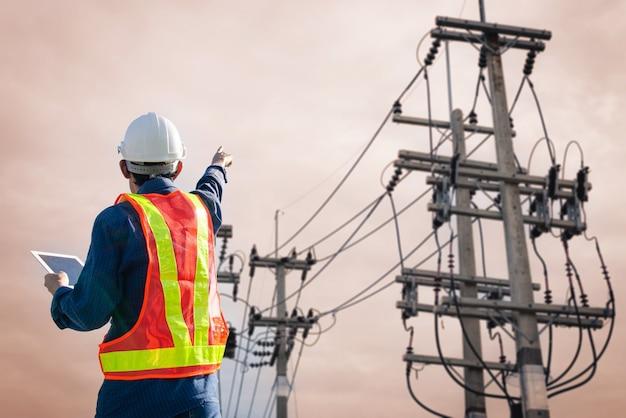 Eletricista aponta para um poste de alta tensão com um tablet na mão.