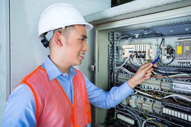 Eletricista asiática no painel no canteiro de obras