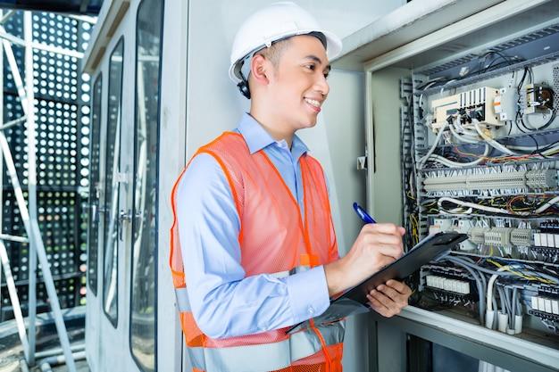 Eletricista asiático no painel no canteiro de obras