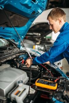Eletricista automotivo com multímetro verifica o nível da bateria.