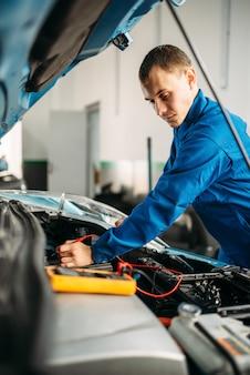 Eletricista automotivo verifica o nível da bateria