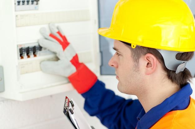 Eletricista caucasiano reparando um plano de energia