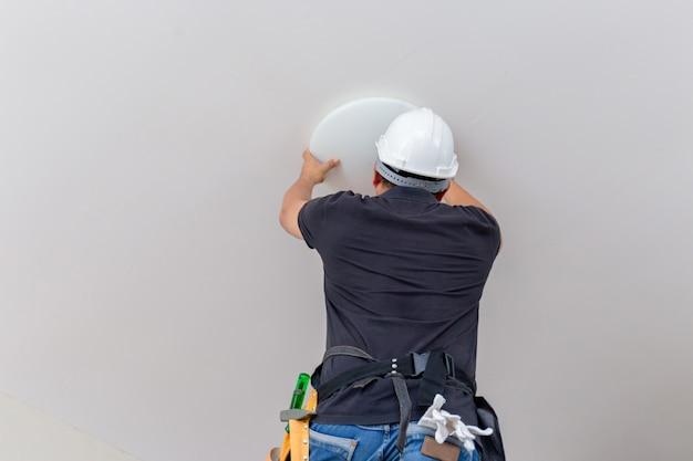 Eletricista com capacete branco que verifica a iluminação no teto na casa, conceito do técnico.