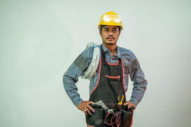 Eletricista com capacete de segurança e um monte de fios dentro de casa.