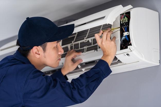 Eletricista com chave de fenda que repara o condicionador de ar dentro de casa