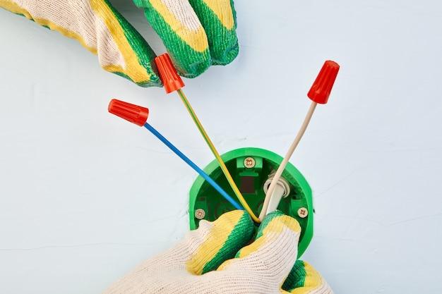 Eletricista com luvas de proteção está colocando fios apertados dentro de uma caixa elétrica redonda para tomada.