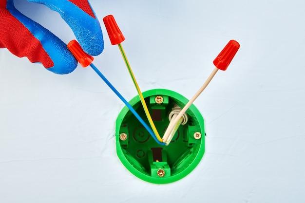 Eletricista com luvas de proteção está montando fios elétricos na instalação elétrica da caixa de soquete