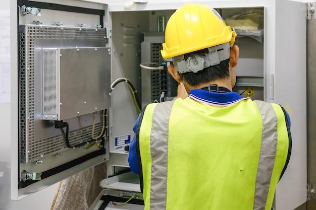 Eletricista com uma macro de chave de fenda conecte os fios do armário elétrico