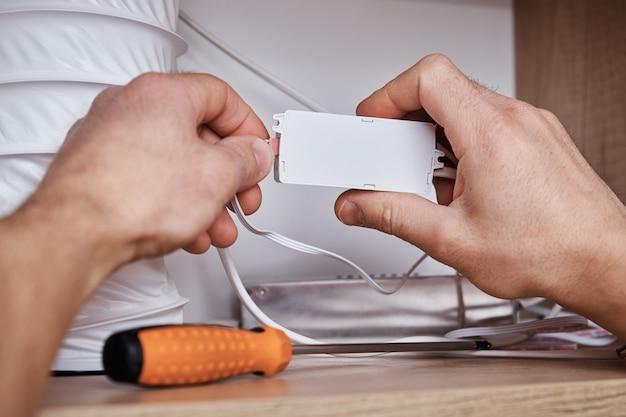 Eletricista conecta o fio no armário da cozinha