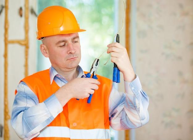 Eletricista consertando a fiação do teto da casa