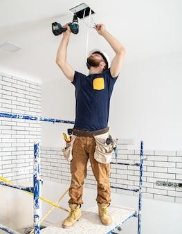 Eletricista construtor em obra, instalação de lâmpadas em altura.