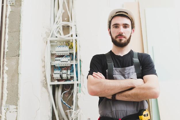 Eletricista de pé em cabos na parede
