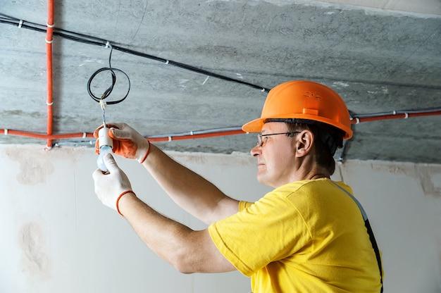 Eletricista definindo uma lâmpada para iluminação temporária