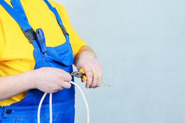 Eletricista em um macacão azul e uma camiseta amarela, segurando um alicate e arame.