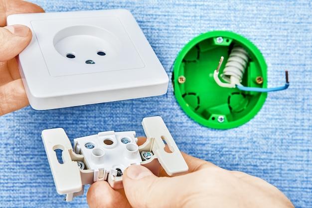 Eletricista está conectando duas partes da nova tomada de padrão europeu com caixa elétrica verde redonda, trabalho elétrico.