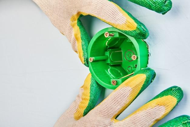 Eletricista está fazendo um novo interruptor ou caixa redonda elétrica de tomada de parede, trabalho de instalação elétrica.