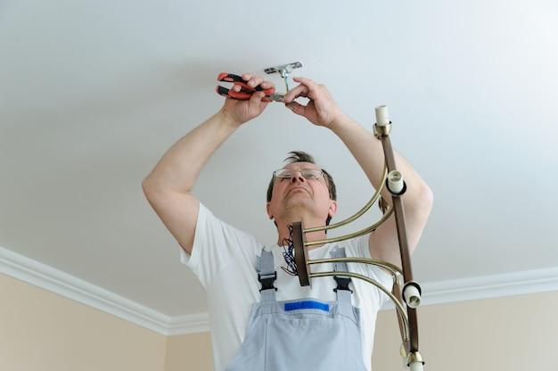 Eletricista está instalando e conectando uma lâmpada