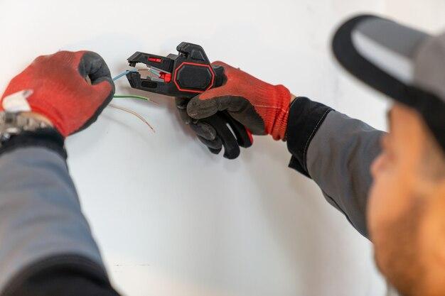 Eletricista expõe bordas de fios com uma ferramenta especial