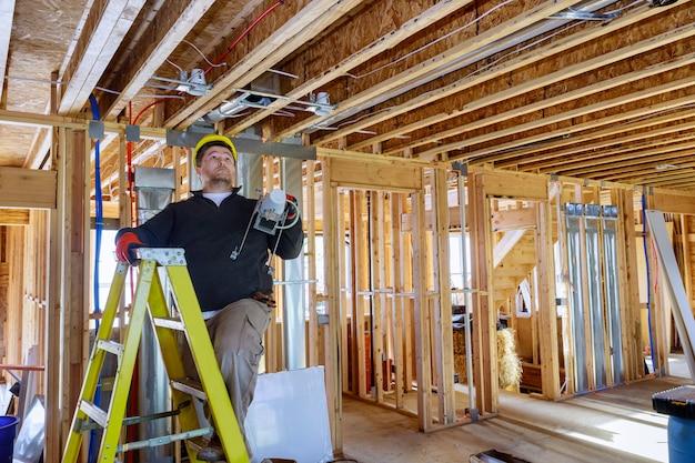 Eletricista instala e monta a iluminação interior no teto