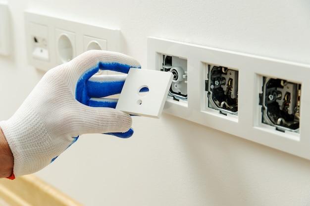 Eletricista instala moldura decorativa.