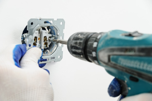 Eletricista instala tomada elétrica.