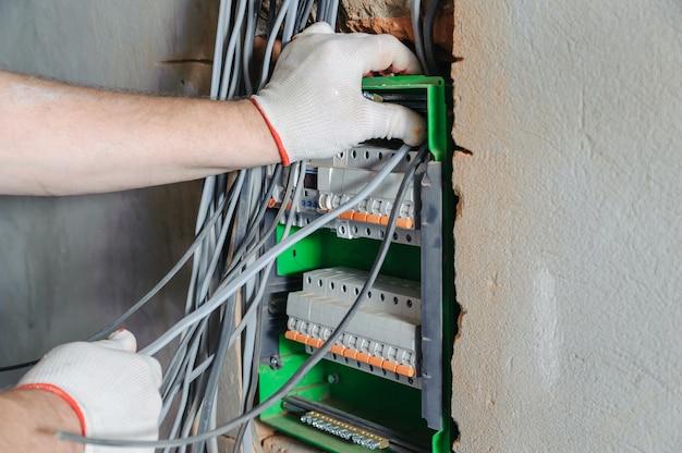 Eletricista instalando fios elétricos em uma caixa de fusíveis de comutação