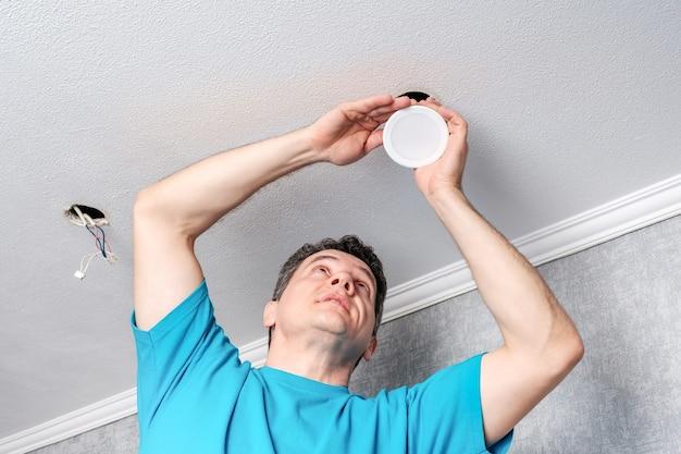 Eletricista instalando focos de led no teto