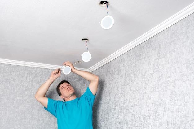 Eletricista instalando modernos refletores de led no teto.