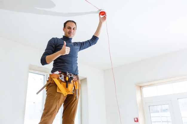 Eletricista instalando sistema de alarme de incêndio dentro de casa