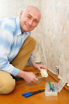 Eletricista instalando soquete de parede na casa