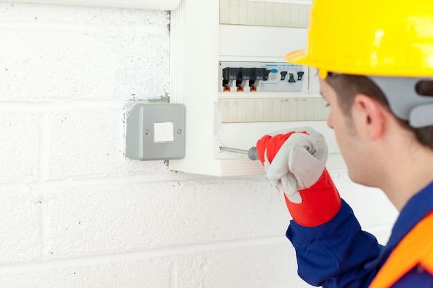 Eletricista madura, reparando um plano de energia
