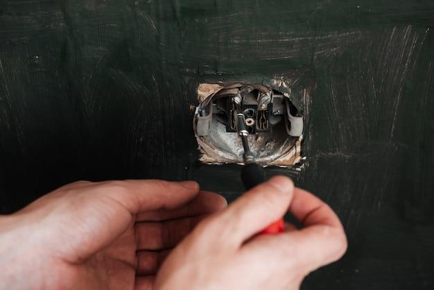Eletricista masculina repara uma tomada elétrica antiga