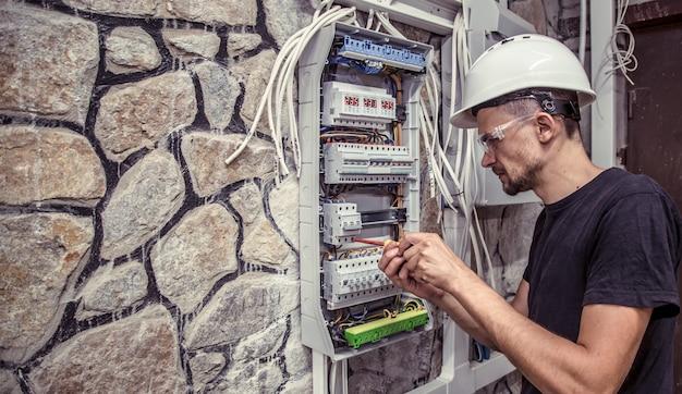 Eletricista masculina trabalha em um quadro de distribuição com uma cabine de conexão elétrica