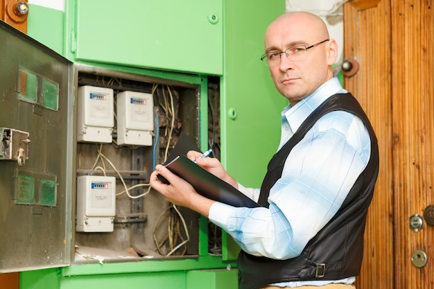 Eletricista no trabalho inspecionando a conexão do cabeamento da linha elétrica de alta tensão na placa do fusível de distribuição