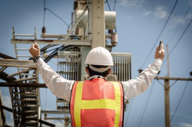 Eletricista orgulhosamente levanta a mão contra o fundo de um transformador montado em um poste de luz.