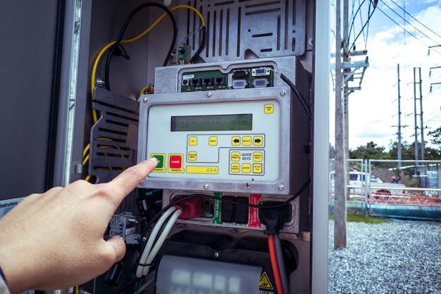 Eletricista perto do gabinete de alta tensão. fonte de alimentação ininterrupta. eletricidade, armários de controle