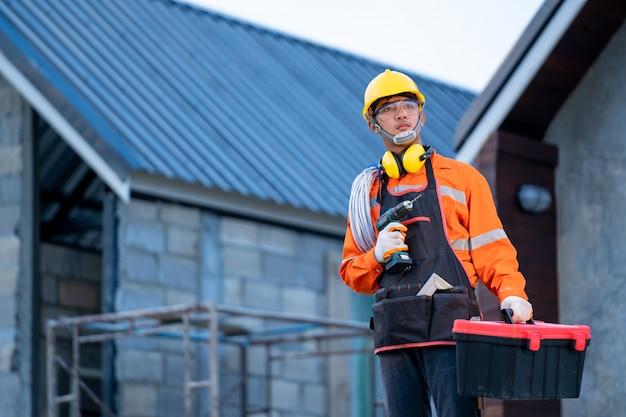 Eletricista que trabalha com a ferramenta no canteiro de obras, na casa e na reconstrução da casa.