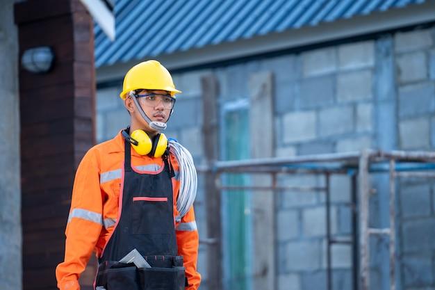 Eletricista que trabalha com capacete e cabo trabalhando em um canteiro de obras, reparo e conceito de trabalhador manual.
