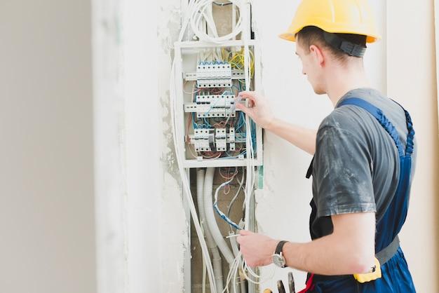 Eletricista que trabalha com painel de distribuição