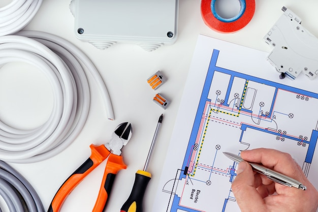Eletricista que verifica os planos elétricos. reparação do conceito de equipamentos elétricos.