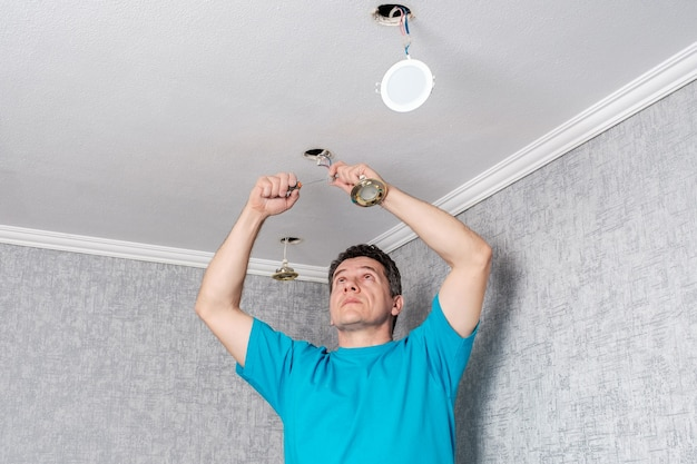Eletricista remove lâmpadas halógenas antigas e ineficientes do teto