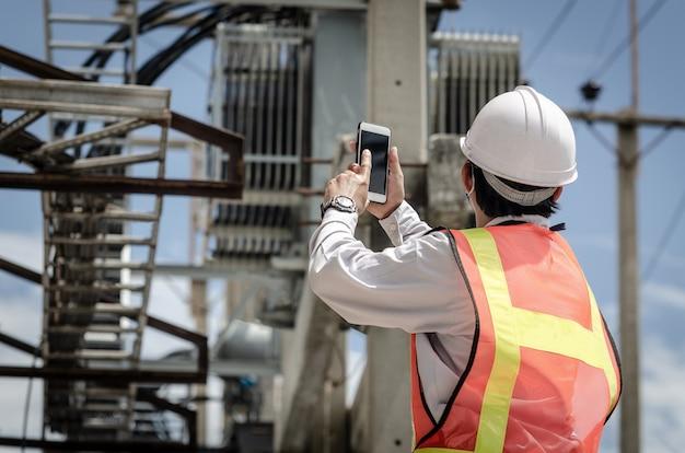 Eletricista segura um smartphone contra o fundo de um transformador montado em um poste de energia